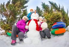 Vue de dessous des enfants s'asseyant près du bonhomme de neige Photos libres de droits
