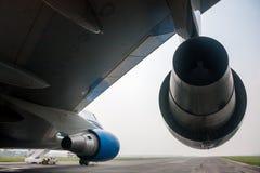 Vue de dessous l'aile d'un grand avion à fuselage large sur l'aéroport de piste Image stock