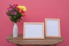 Vue de deux photos sur un en bois et des fleurs dans le pot sur le fond rose Photographie stock