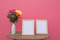 Vue de deux photos sur un en bois et des fleurs dans le pot sur le fond rose Photos stock