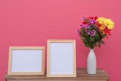 Vue de deux photos sur un en bois et des fleurs dans le pot sur le fond rose Photos libres de droits