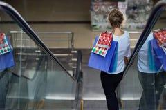 Vue de dos de client avec des paniers entraînant une réduction sur l'escalator dans le mail images libres de droits