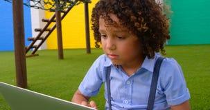 Vue de face d'écolière de métis étudiant sur l'ordinateur portable dans le terrain de jeu 4k d'école banque de vidéos