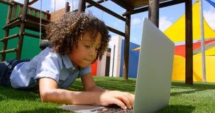 Vue de face d'écolière de métis étudiant sur l'ordinateur portable dans le terrain de jeu 4k d'école clips vidéos