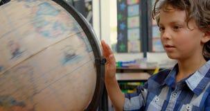 Vue de face d'écolier caucasien étudiant le globe au bureau dans la salle de classe à l'école 4k banque de vidéos