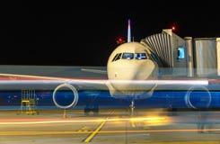 Vue de face d'avions modernes dans la nuit, le concept de la tache floue et personnes brouillées autour Photographie stock libre de droits