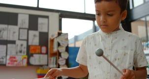 Vue de face d'?colier asiatique jouant le xylophone dans une salle de classe ? l'?cole 4k clips vidéos