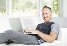 Vue de face d'un homme bel à l'aide de l'ordinateur portable se reposant sur le divan à la maison images stock