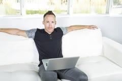 Vue de face d'un homme bel à l'aide de l'ordinateur portable se reposant sur le divan à la maison photo stock