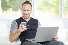 Vue de face d'un homme bel à l'aide de l'ordinateur portable se reposant sur le divan à la maison photographie stock libre de droits