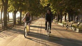 Vue de face d'un jeune couple heureux ou des amis montant leurs vélos dans le parc ou le boulevard de ville dans l'été Les gens banque de vidéos