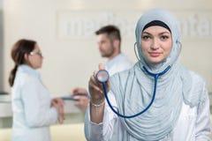 Vue de face d'une femme arabe de docteur montrant le stéthoscope Photo stock