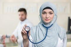 Vue de face d'une femme arabe de docteur montrant le stéthoscope Photographie stock libre de droits