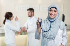 Vue de face d'une femme arabe de docteur montrant le stéthoscope image stock