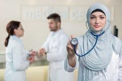 Vue de face d'une femme arabe de docteur montrant le stéthoscope Photo libre de droits