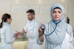 Vue de face d'une femme arabe de docteur montrant le stéthoscope Images stock