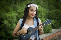 Vue de face d'une jeune belle fille avec les cheveux tressés, jouant l'ukulélé photographie stock