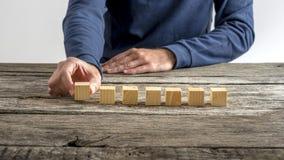 Vue de face d'une main masculine plaçant sept cubes en bois en blanc dans a Photo stock