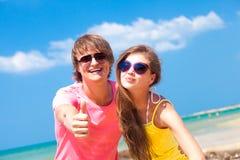 Vue de face de jeunes couples heureux sur le sourire de plage Image libre de droits