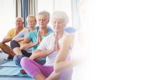 Vue de face des aînés détendant avec l'instructeur de forme physique Images libres de droits