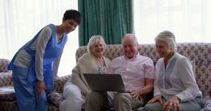 Vue de face des amis supérieurs caucasiens actifs et du docteur féminin utilisant l'ordinateur portable dans la maison de repos 4 banque de vidéos