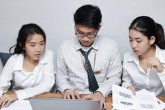 Vue de face des gens d'affaires asiatiques travaillant ensemble sur un ordinateur portable au bureau Concept brainstroming de tra Images stock