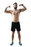 Vue de face du jeune athlète barbu d'ajustement fléchissant des muscles images libres de droits