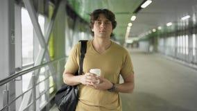 Vue de face du jeune homme avec le sac et du café marchant dans le tunnel clips vidéos