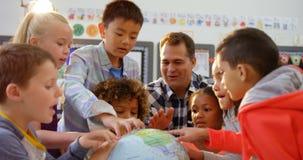Vue de face du professeur masculin caucasien enseignant les enfants au sujet du globe dans la salle de classe 4k banque de vidéos