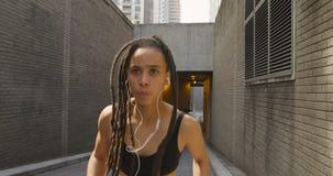 Vue de face de femme d'Afro-américain pulsant dans la ville 4k banque de vidéos