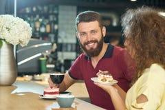 Vue de face de garçon de sourire avec du café potable de barbe avec la fille bouclée photographie stock libre de droits