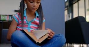 Vue de face de l'écolière attentive d'Afro-américain lisant un livre dans la bibliothèque à l'école 4k banque de vidéos