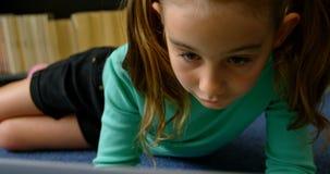 Vue de face de l'écolière caucasienne attentive étudiant avec l'ordinateur portable dans la bibliothèque à l'école 4k banque de vidéos
