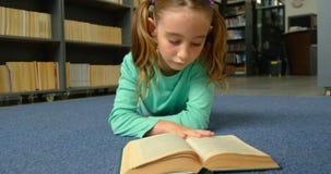 Vue de face de l'écolière caucasienne attentive lisant un livre dans la bibliothèque à l'école 4k clips vidéos