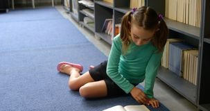Vue de face de l'?coli?re caucasienne attentive lisant un livre dans la biblioth?que ? l'?cole 4k banque de vidéos