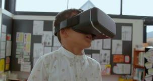 Vue de face de l'?colier asiatique ? l'aide du casque de r?alit? virtuelle dans la salle de classe ? l'?cole 4k clips vidéos