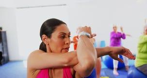 Vue de face de l'entraîneur féminin caucasien formant les personnes supérieures dans l'exercice au studio 4k de forme physique banque de vidéos