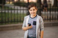 Vue de face de support riant d'adolescent dans la ville avec le smartphone photos libres de droits