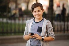 Vue de face de support riant d'adolescent dans la ville avec le smartphone photos stock