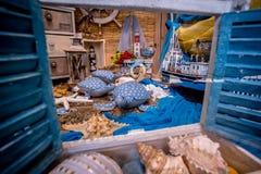Vue de fenêtre avec les volets bleus de fenêtre sur orienté grec avec les tortues faites main, les coquilles et les bateaux photos stock