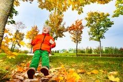 Vue de garçon de dessous se reposer sur des oscillations en parc Photographie stock