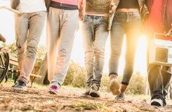 Vue de jambes des amis marchant en parc de vélo de ville avec le contre-jour Photo stock