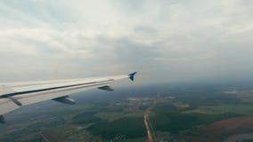 Vue de l'aile blanche du vol d'avions au-dessus des champs verts et des petits règlements banque de vidéos