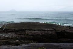 Vue de l'Océan Atlantique avec des vagues se brisant les roches et l'île sur le brackground photographie stock libre de droits
