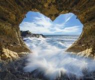 Vue de l'océan d'un caverne-symbole en forme de coeur de jour d'amour et de ` s de Valentine Photographie stock