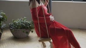 Vue de la femme enceinte qui dans une longue robe rouge balançant sur l'oscillation près de la grande fenêtre Conception de gross banque de vidéos