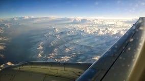 Vue de la fenêtre d'avion des montagnes avec la neige sur le dessus, les nuages, l'aile et le ciel bleu Pour le concept de voyage Images stock