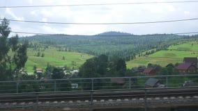 Vue de la fenêtre d'un train mobile à un village dans les montagnes carpathiennes banque de vidéos