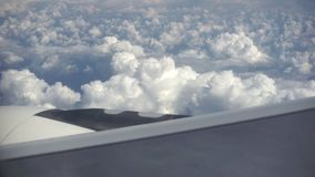 Vue de la fenêtre d'une haute de vol d'avion au-dessus le moulu, beau, de tas, de nuages blancs et de ciel banque de vidéos