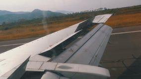 Vue de la fenêtre sur l'aile d'un avion se déplaçant le long de la piste à l'aéroport après le débarquement clips vidéos